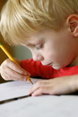 Young Child Drawing on Paper with Pencil — Stock Photo