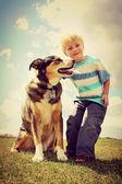 Niño feliz fuera con su perro — Foto de Stock