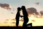Mother Lovingly Kissing Little Child at Sunset — Stock Photo