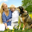 Laughing Mother and Child Playing with Dog — Stock Photo #46478639