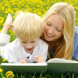 Happy Mother and Child Reading Book Outside in Meadow — Stock Photo #46479023