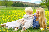 Mother and Young Child Relaxing in Flower Meadow — Stock Photo