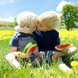 Young Children HUgging as they Eat Fruit Outside — Stock Photo