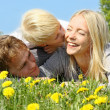 Mother, Father and Child Hugging and Kissing in Flower Meadow — Stock Photo #47169905