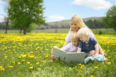 Mother Reading Story Book to Two Young Children Outside in Meado — Stock Photo