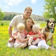 Portrait of Happy Family and Dog in Flower Meadow — Stock Photo