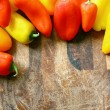 A collection of Red and Yellow Sweet Peppers BorderingWood Cutti — Stock Photo #48622719