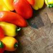A collection of Red and Yellow Sweet Peppers Bordering Wood Cutt — Stock Photo #48622801