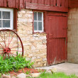 Antique Wagon Wheel Leaning on Old Stone Barn Wall — Stock Photo #48948659