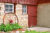 Antique Wagon Wheel Leaning on Old Stone Barn Wall — Stock fotografie