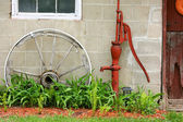 Antique Wooden Wagon Wheel and Water Pump by Barn — Stock fotografie