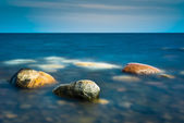 Three rocks in the calm water — Stock Photo