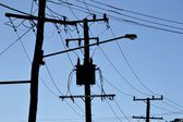 Silhouette of telephone poles and power lines — Stock Photo