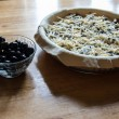 Preparation of pie (the dough, fish and grated cheese into a glass baking dish, near glass cup with olives) — Stock Photo #26216625