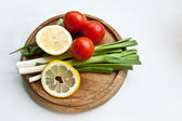 Fresh vegetables (onions, tomato and lemon) on acutting board — Stock Photo