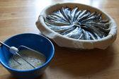 Preparación del pastel (pasta y pescado en un asadera, cerca de la taza con huevos batidas de vidrio) — Foto de Stock
