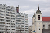 Multistorey apartment building and the Christian church — Stock Photo