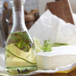 Stock Photo: Bottle of oil with herbs and cheese