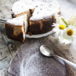 Cheesecake on a glass dish whith bouquet of camomile — Stock Photo