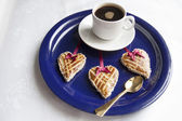 Three cookies in the shape of heart on the blue plate — Stock Photo
