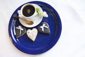 Three wedding cookies with a cup of coffee on the blue plate — Stock Photo
