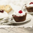Chocolate dessert decorated with cream and a cherry — Stock Photo
