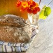 Bread, flowers and pumpkin on old wooden table — Stock Photo