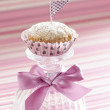 Stock Photo: Pumpkin cupcake on glass cup decoreted with satin silk bow