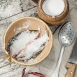 Stock Photo: Two roaches fish in ceramic bowl with salt.