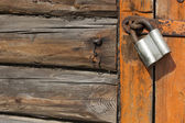 Old wooden door with padlock, fragment — Stock Photo