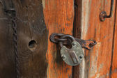 Old wooden door with padlock, fragment — Zdjęcie stockowe