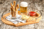 Garlic cheese bread sticks and cup of beer — Stock Photo