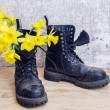 Black military muddy shoes with yellow narcissus — Stock Photo #44298117