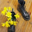 Black military muddy shoes with yellow narcissus — Stock Photo #44298131