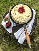 Pancakes with red currants on old pan and spoon — Photo