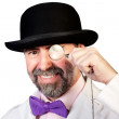 Happy looking man with a monocle in his hand — Stock Photo