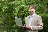 Portrait of happy middle-aged businessman holding notebook and s — Stock Photo