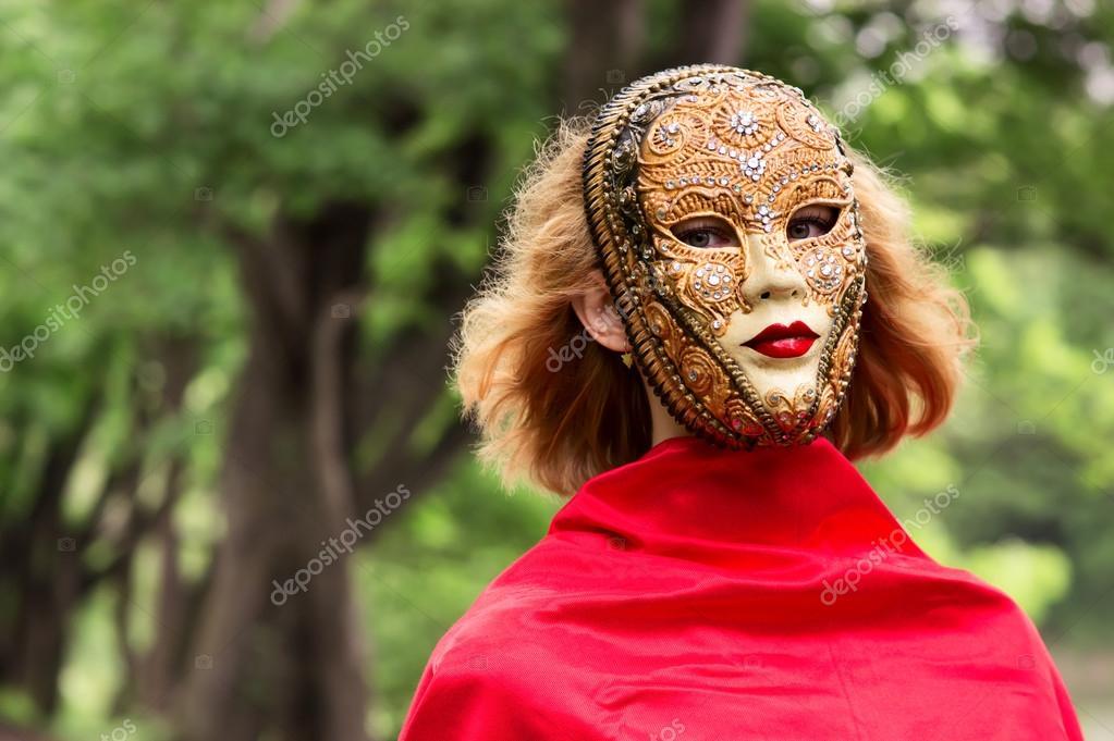 嘉年华面具在树叶背景的金发女人 - 图库图片