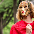 Blond woman in carnival mask over foliage background — Stock Photo