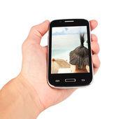 Hand holding slimme telefoon, naturistenvakantie roepen. geïsoleerd op witte ba — Stockfoto