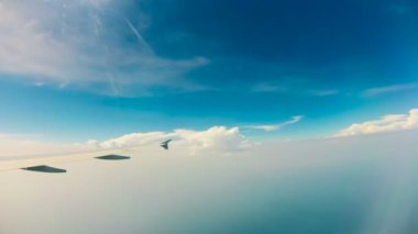 View of blue sky and wing of plane flying through clouds, Time Lapse — Wideo stockowe