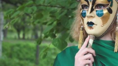 Beautiful woman in carnival mask over foliage background — Stock Video