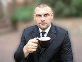 A man with a cup in his hand — Stockfoto