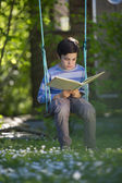 Child reading a book outdoors — Stok fotoğraf