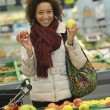 Woman buys fruit and food in the supermarket — Stok fotoğraf