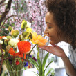 Consumerism: Woman smelling fresh flowers. — Stock Photo
