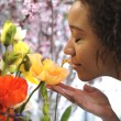 Consumerism: Woman smelling fresh flowers. — Stock Photo #36247595