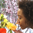 Stock Photo: Consumerism: Woman smelling fresh flowers.