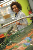 Woman buys vegetable and food in the supermarket — Stockfoto