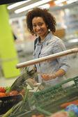 Mulher compra comida no supermercado e vegetais — Fotografia Stock